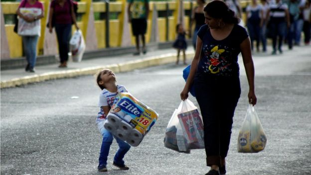 a child struggles with an 18-pack of toilet paper next to a woman carrying multiple plastic bags, 10 July 2016