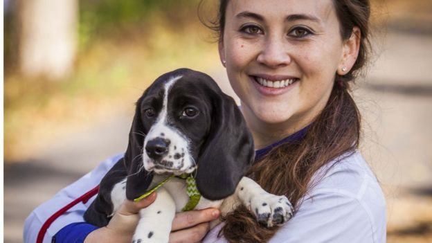 Cornell scientist Jennifer Nagashima with a beagle-spaniel pup