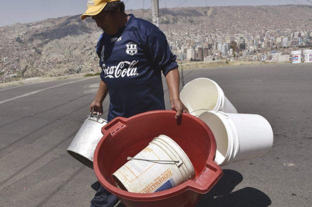 Hombre cargando muchos recipientes para recibir agua.