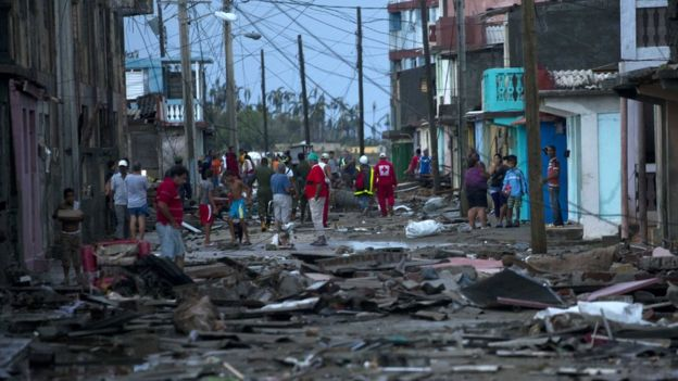 Red Cross workers and residents walk among the damage caused by Hurricane Matthew in Baracoa, Cuba, Wednesday, Oct. 5, 2016