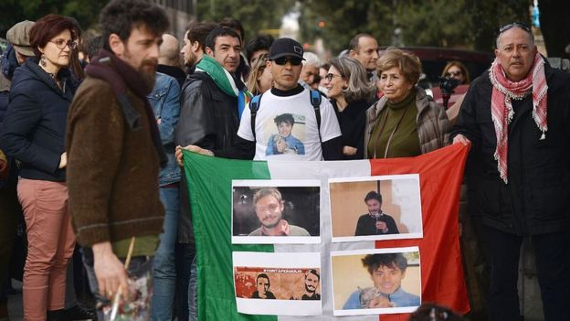 People hold an Italian flag with photos of Giulio Regeni during a demonstration in front of the Egypt's embassy in Rome on 25 February 2016