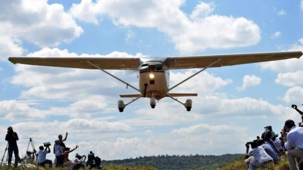 People take pictures and watch a vintage flying low over the Nairobi National Park, in Nairobi (27 November 2016)