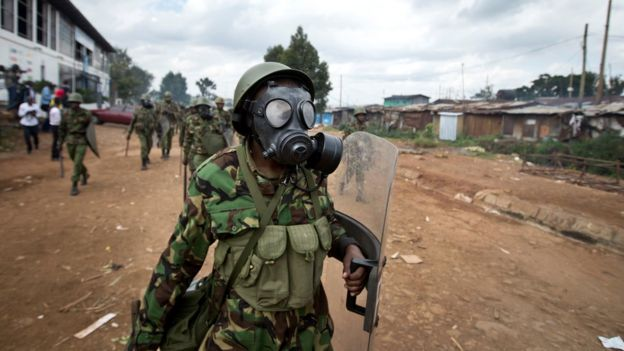 A Kenyan policeman wearing a gas mask chases protesters throwing rocks, in the Kibera slum of Nairobi