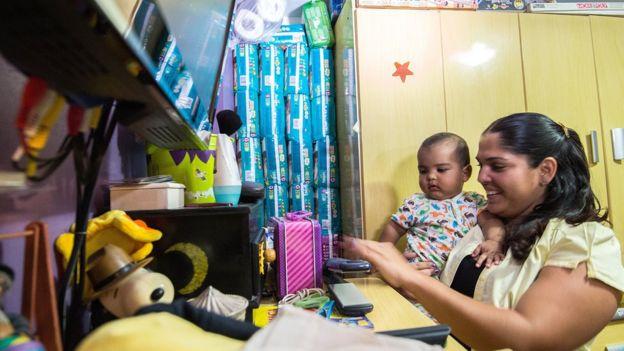 Una mujer con un bebé en casa, donde guarda bolsas de pañales