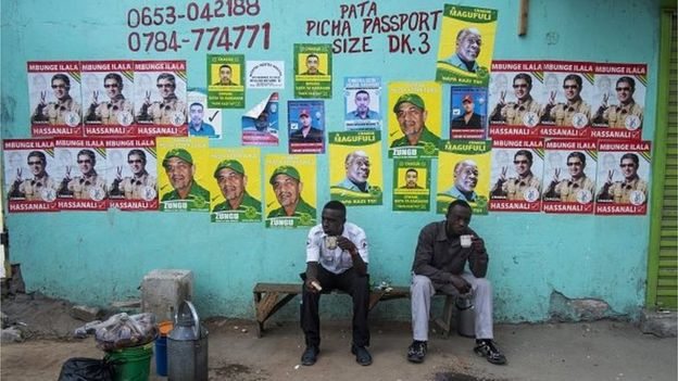 Men take a tea break in front of a wall with election posters near a polling station in Dar es Salaam on 25 October, 2015, during the Tanzanian presidential election