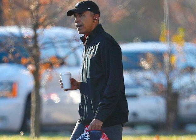 Obama en una caminata con un café en la mano.