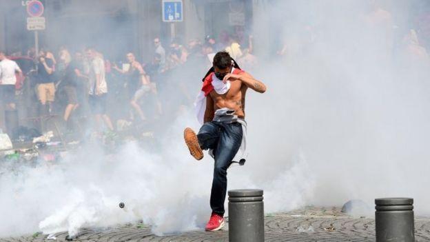 England fan kicks a can of tear gas away