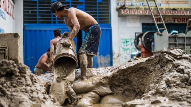 Hombre botando lodo de su propiedad con ayuda de un balde.