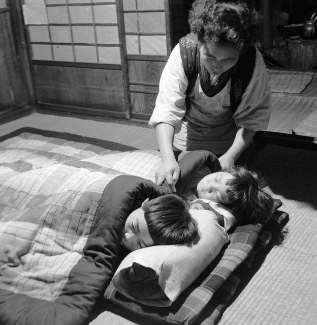 Niños japoneses en la cama y una mujer