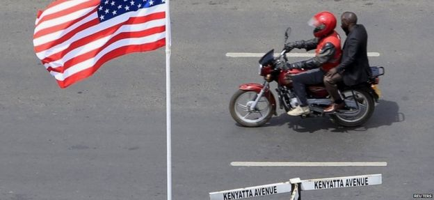 A motorcyclist rides past a US flag at a main street as the country prepares to receive U.S. President Barack Obama for his three-day state visit, in Kenya's capital Nairobi 24 July 2015