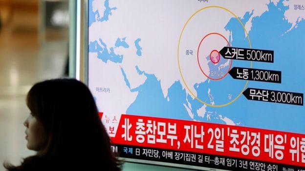 Una mujer pasa por adelante de un televisor donde se ven noticias de Corea del Sur sobre el nuevo lanzamiento de misiles de parte de Corea del Norte.