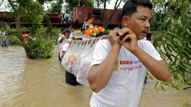volunteers carry aid for flood victims at KanGyi village in Kanbalu, Sagaing Division, Myanmar, 21 July 2015.