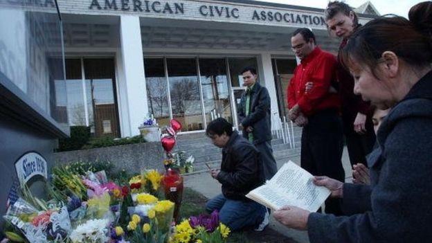 Un grupo de personas reza frente al centro comunitario de migrantes, en Binghamton, Nueva York, tras la masacre, en 2009.