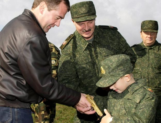 Russian President Dmitry Medvedev (left) and his Belarusian counterpart Alexander Lukashenko (C) interact with Lukashenko's five-year-old son Kolya at the Obuz-Lesnovsky firing range near Baranovichi in September 2009