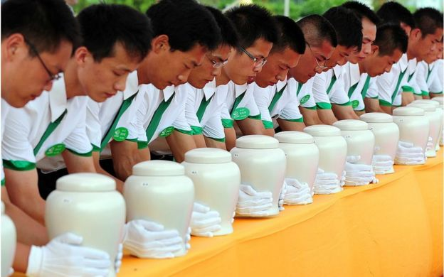 Attendants place biodegradable urns on a table at a cemetery in Tianjin, northern China, for a collective eco-burial on 20 July 2010.