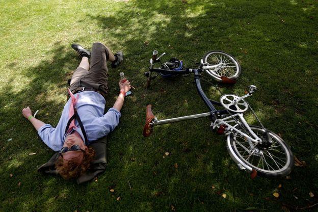 Un ciclista descansa junto a su bicicleta Brompton