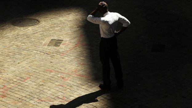 Un hombre con expresión abatida, cuya sombra se proyecta en el piso, en claroscuro