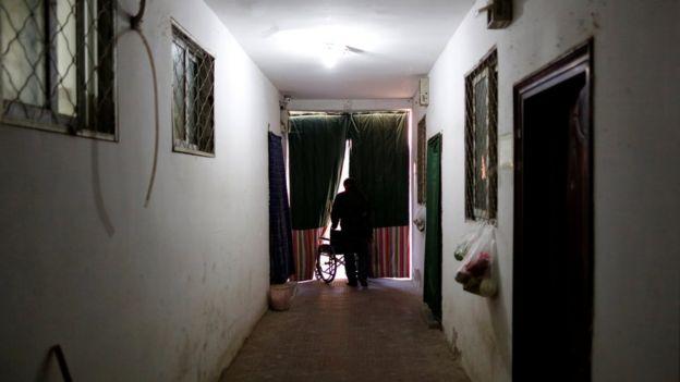 Hombre empuja una silla de ruedas a través de unas cortinas oscuras, al final de un pasillo.