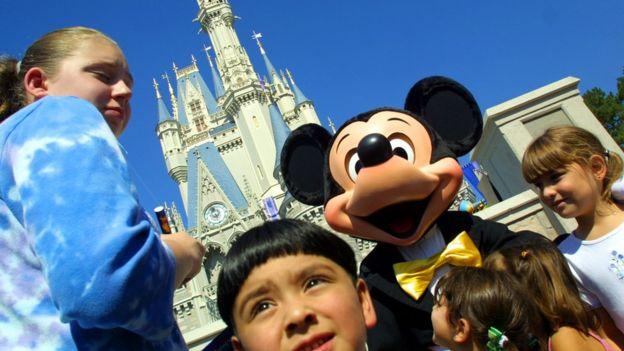 niños sonríen al lado de Mickey mouse y en el fondo el castillo Disney