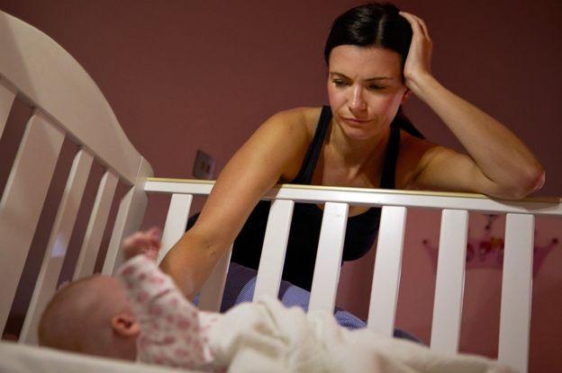 Una madre cansada trata de dormir a su hijo.
