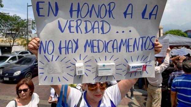 Una señora con una pancarta que denuncia la escasez de medicamentos