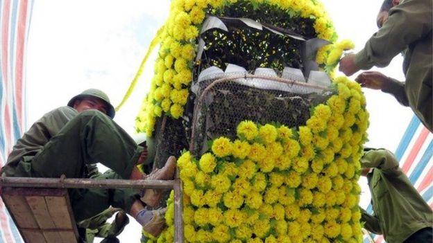 Công nhân tháo dỡ hoa phần đầu rồng để chỉnh sửa