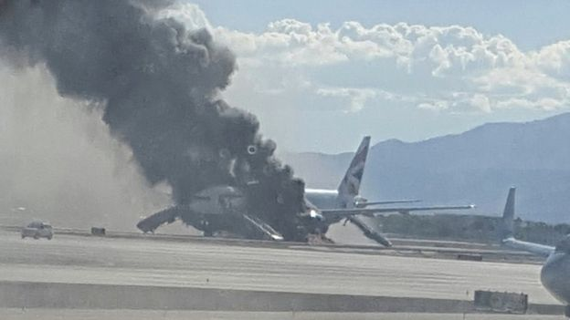 The view of a plane window, smoke billows out from a plane that caught fire at McCarren International Airport, 8 September 2015