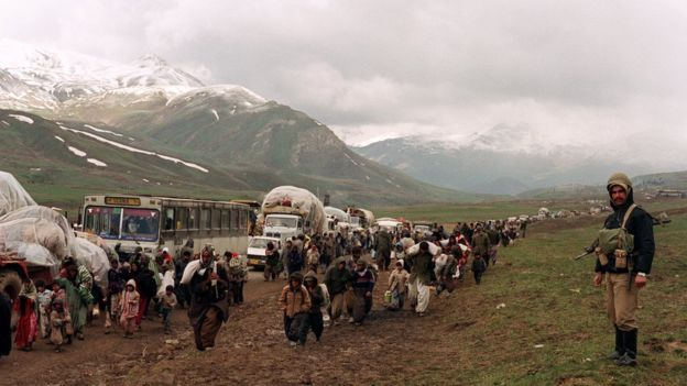 Thousands of Iraqi Kurdish refugees cross the Iraq-Iran border at Hadji Omran point near Piranshar 12 April 1991