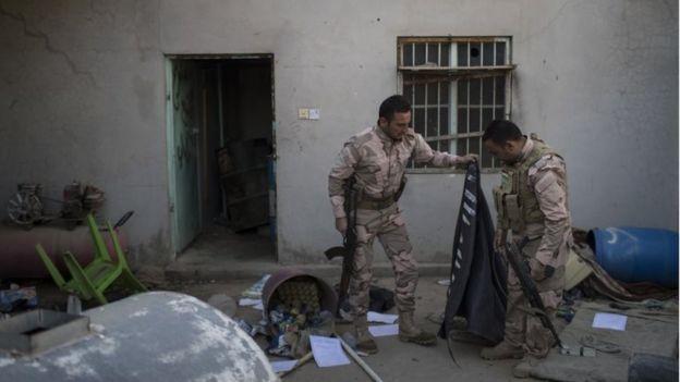 Combatientes kurdos peshmerga sostienen una bandera de Estado Islámico abandonada en una casa de Faziliya, al norte de Mosul, en Irak, el 2 de noviembre de 2016.