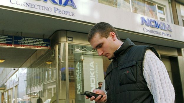 A man uses his mobile in front of a Nokia store in 2001