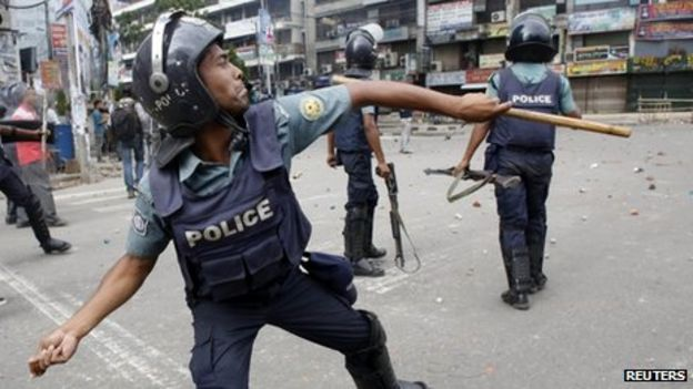 A policeman throws a piece of brick during a clash with activists in Dhaka, 5 May 2013