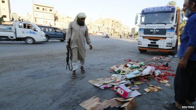 Islamic State fighter throws confiscated goods away in Raqqa, Syria (14 August 2014)