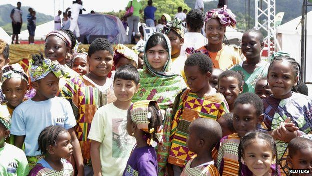 Pakistani schoolgirl activist Malala Yousafzai poses for a photo with children attending a workshop, during her visit to the Emancipation Village at Queen
