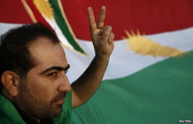 A man gestures in front of the flag of Kurdistan at a demonstration in Athens, Greece (13 October 2014)