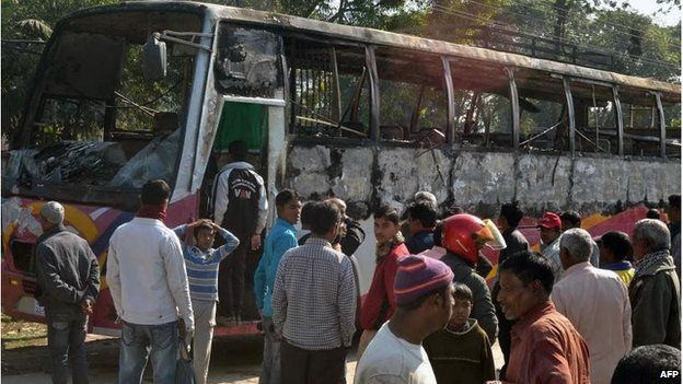 Onlookers surround the wreckage of a burnt bus allegedly set on fire by Bangladesh Nationalist Party (BNP) supporters during a blockade in Rangpur on January 14