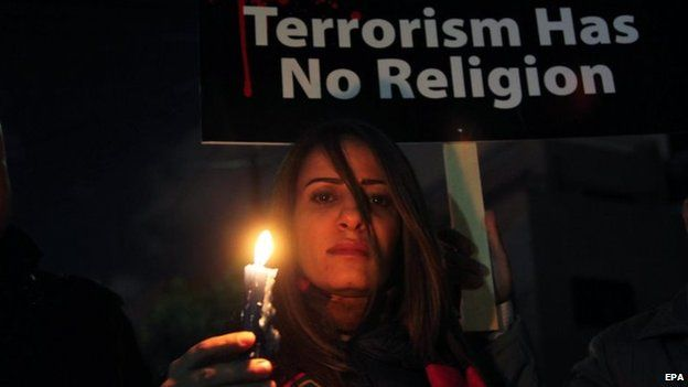 A Jordanian woman holds a candle during a gathering in front of the Egyptian embassy in Amman, Jordan, 17 February 2015