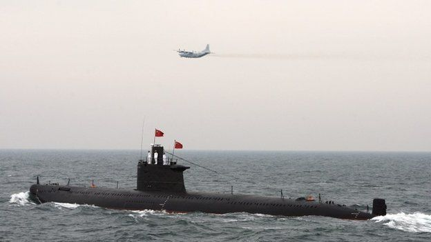 A military aircraft flies past a Chinese Navy submarine