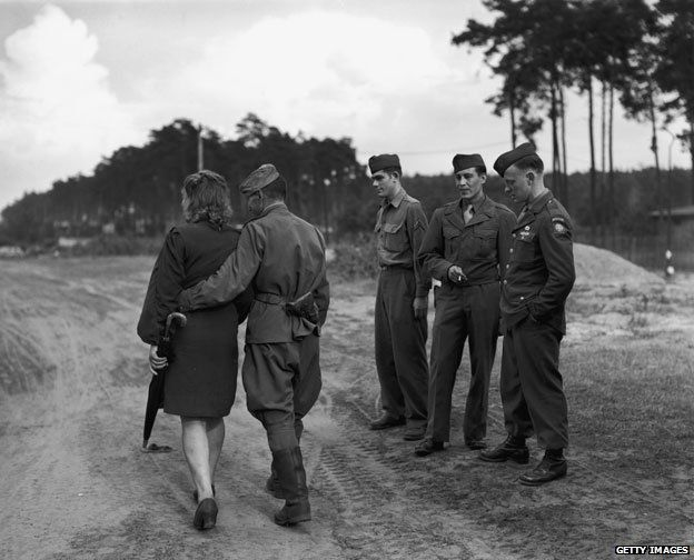 Circa 1945: GIs watch one of their Russian allies as he goes out walking with his girlfriend in Berlin