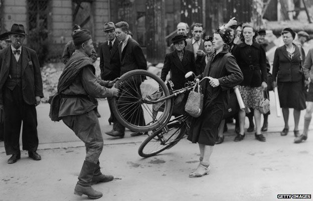 A Soviet soldier struggles to take a woman's bicycle in Berlin