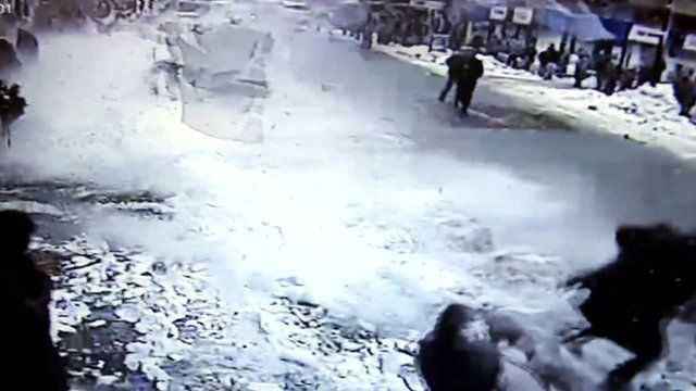 Chunks of snow fall off a roof onto pedestrians in Rize, Turkey