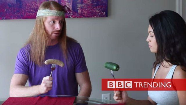Image from video 'If Meat Eaters Acted Like Vegans'. Man holding sausage, woman holding cucumber.
