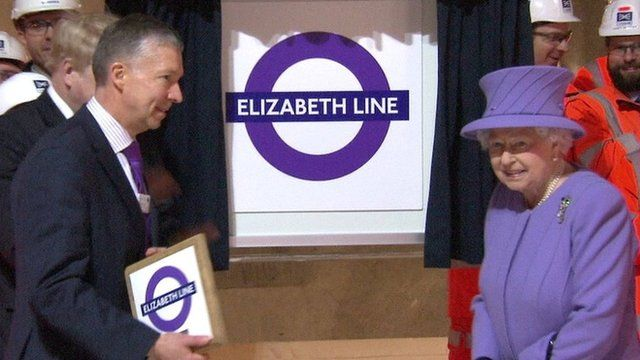 The Queen beside new logo for the line