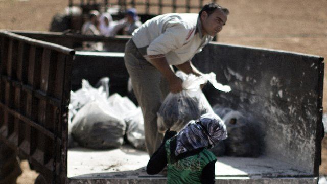 Syrian farmers load bags of dried waste of pressed olives mixed with water in a field near the battled Syrian city of al-Bab