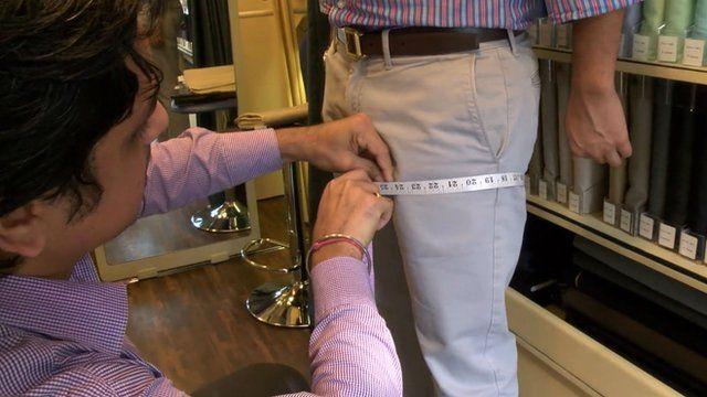 Tailor measures a customer