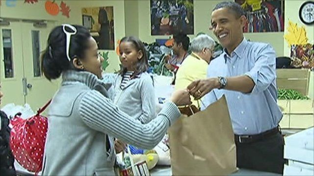 Obama hands a bag of food to a woman