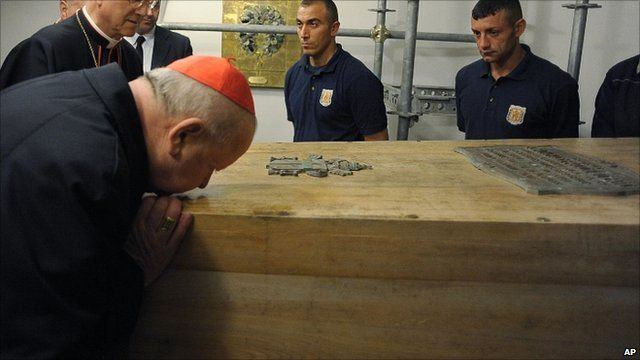 Cardinal Stanislaw Dziwisz kisses the coffin of Pope John Paul II