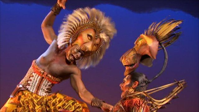 Cast from the Lion King performing on stage