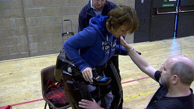 Elena Bertoldo is helped into the bionic legs by Richard Little