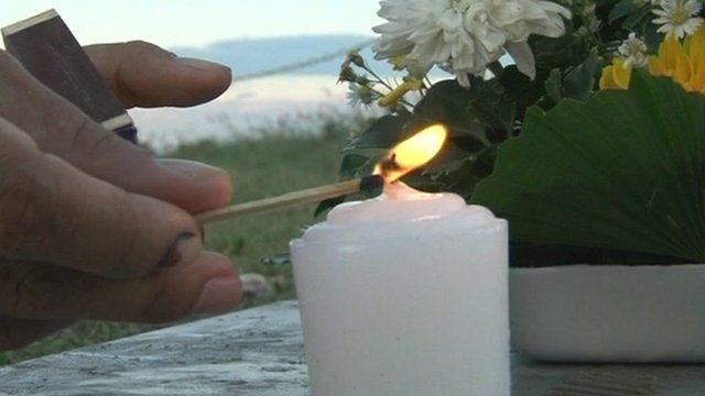Memorial candle being lit