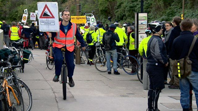 Unicyclist carrying a placard